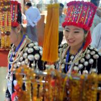 Kachin ethnic women view amber necklaces and bracelets during the annual gems and jewelry exposition in Naypyidaw on June 20. | AFP-JIJI