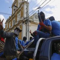 Armed pro-government militia members flash victory signs as they occupy the Monimbo neighborhood of Masaya, Nicaragua, Wednesday. On Tuesday, Nicaraguan government forces retook the symbolically important neighborhood that had become a center of resistance to Nicaraguan President Daniel Ortega's government. | AP