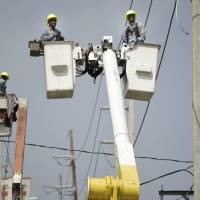A brigade from the Electric Power Authority repairs distribution lines damaged by Hurricane Maria in the Cantera community of San Juan, Puerto Rico, on Oct. 19.   AP