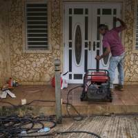 Leonardo Pagan works with his power generator outside his home in Adjuntas, Puerto Rico, on July 12, 2018. The community leader has been powering up his neighbors by connecting extension chords to his generator and extending the line to their property. | AP