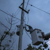 A laborer from the Puerto Rico Power Authority works to restore power in Adjuntas, Puerto Rico, on July 12, 2018. Puerto Rico's electrical grid is still shaky after Hurricane Irma brushed past the island as a Category 5 storm last Sept. 6 and then Hurricane Maria made a direct hit as a Category 4 storm two weeks later, damaging up to 75 percent of transmission lines. | AP