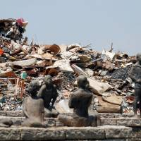 Household waste collected in the wake of the heavy flooding in western Japan is piled up at a temporary collection site in Kurashiki, Okayama Prefecture, on Saturday.   REUTERS
