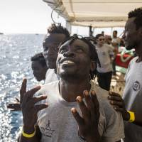Migrants aboard the Open Arms aid boat, of Proactiva Open Arms Spanish NGO, react as the ship approaches the port of Barcelona, Spain, Wednesday. The aid boat sailed to Spain with 60 migrants rescued on Saturday in waters near Libya, after it was rejected by both Italy and Malta. | AP