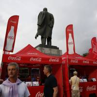 Booths marketing products by event sponsors Budweiser and Coca-Cola stand beside a statue of Lenin on Wednesday, as fans arrive for the semifinal match between Croatia and England at Luzhniki Stadium during the 2018 soccer World Cup in Moscow. | AP
