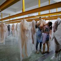 Workers hang a sex doll in the warehouse at the WMDOLL factory in Zhongshan, Guangdong Province, China, on July 11. | REUTERS