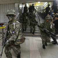 South Korean army soldiers conduct an anti-terror drill inside a subway station in Seoul in 2017. | AP