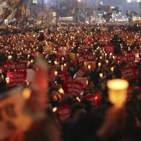 South Korean protesters hold up candles during a rally calling for South Korean President Park Geun-hye to step down in Seoul on Nov. 19, 2016. | AP