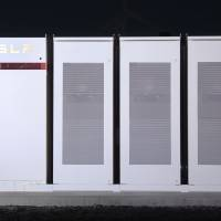 Tesla Inc. Powerpacks that will be used to form the world's largest lithium-ion battery stand on display at the Hornsdale wind farm near Jamestown, South Australia, on Sept. 29, 2017. | BLOOMBERG
