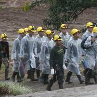 Rescuers walk toward the entrance to a cave complex where five were still trapped in Thailand on Tuesday. | AP
