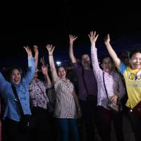 Volunteers celebrate at a makeshift press center in the Mae Sai district of Thailand's Chiang Rai province Tuesday night after the last boys and their soccer coach were rescued from a cave. | AFP-JIJI
