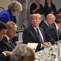U.S. President Donald Trump looks back at British Prime Minister Theresa May, at the Art and History Museum at the Park Cinquantenaire in Brussels on Wednesday. NATO leaders gathered in Brussels Wednesday for a two-day summit to discuss Russia, Iraq and their mission in Afghanistan. | GEERT VANDEN WIJNGAERT, POOL / VIA AP