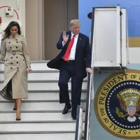 U.S. President Donald Trump and first lady Melania Trump disembark Air Force One as they arrive at Melsbroek Military airport in Melsbroek, Belgium, Tuesday. President Trump is in Brussels to attend a two-day NATO summit. | AP