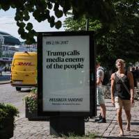People walk next to an advertising board reading 'Trump calls media enemy of the people' on the sidelines of a meeting between U.S. President and his Russian counterpart on Monday in Helsinki. | AFP-JIJI