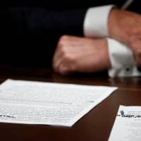U.S. President Donald Trump's prepared remarks show his own handwritten note 'There was no collusion' at the top as he speaks about his summit meeting with Russian President Vladimir Putin at the start of a meeting with members of the U.S. Congress at the White House in Washington Tuesday. | REUTERS