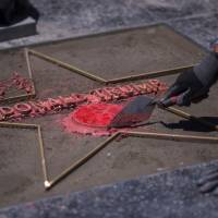 Workers replace the star of U..S President Donald J. Trump on the Hollywood Walk of Fame after it was destroyed by a vandal in the early morning hours on Wednesday in Los Angeles. | AFP-JIJI