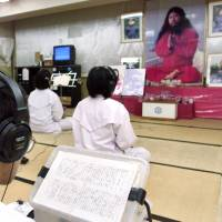 Followers of doomsday cult Aum Shinrikyo chant before a portrait of guru Shoko Asahara during religious training at Aum's Adachi Ward office in Tokyo in July 1999. | REUTERS