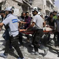 White Helmet rescue workers move a victim after airstrikes in Syria in September 2016. | SYRIAN CIVIL DEFENSE WHITE HELMETS / VIA AP