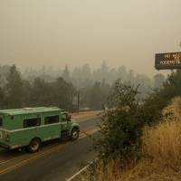 A fire transport drives along Highway 140, one of the entrances to Yosemite National Park, on July 16, 2018, in Mariposa, California. The road remains closed as crews battle a deadly wildfire burning near the west end of Yosemite National Park. | AP