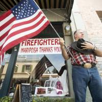 Charles Phillips waits for a procession carrying the body of firefighter Braden Varney on July 16, 2018, in Mariposa, California. Varney died Saturday while battling the Ferguson fire when his bulldozer overturned. | AP
