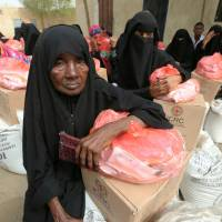 Women sit next to food aid delivered by the International Committee of the Red Cross to internally displaced people in the Red Sea port city of Hodeidah, Yemen, Saturday.   REUTERS