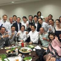 A photo posted on the Twitter account of Deputy Chief Cabinet Secretary Yasutoshi Nishimura shows Prime Minister Shinzo Abe and other Liberal Democratic Party lawmakers attending a private party held in Tokyo on Thursday. | TWITTER / VIA KYODO