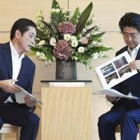 Ehime Gov. Tokihiro Nakamura briefs Prime Minister Shinzo Abe in Tokyo on damage caused by the floods and landslides triggered by recent heavy rain in western Japan. | KYODO