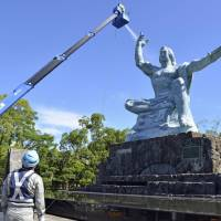 The Peace Statue in Nagasaki Peace Memorial Park gets cleaned on July 10 in preparation for the annual ceremony held to mark the U.S. atomic bombing of the city on Aug. 9. | KYODO