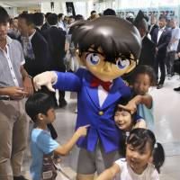 Children play with a mascot from the long-running comic book and anime series 'Detective Conan' at the revamped Tottori Sand Dunes Conan Airport in Tottori Prefecture on Saturday. | KYODO