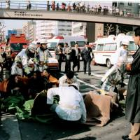 People receive treatment in front of Tsukiji Station in Tokyo on March 20, 1995, after a sarin gas attack by the Aum Shinrikyo cult. | KYODO