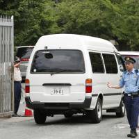 A van believed to be carrying Shoko Asahara's cremated remains enters Tokyo Detention House on Monday morning. | KYODO