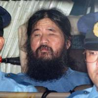 Shoko Asaharais seen in a police vehicle at the Metropolitan Police Department in September 1995, following his arrest in May the same year. | KYODO
