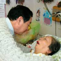 Yoshiyuki Kono (left), a victim of Aum Shinrikyo's 1994 nerve gas attack in Matsumoto, Nagano Prefecture, speaks to his wife, Sumiko, in March 2008. Sumiko Kono, who was left in coma due to the attack, died in August the same year. | KYODO