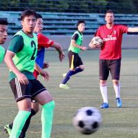 Matteo Cont, an Italian coach from AC Milan, supervises members of Nagoya International Junior and Senior High School's soccer team in Nisshin, Aichi Prefecture. | CHUNICHI SHIMBUN