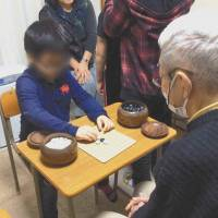 A child with developmental disabilities takes part in 'go therapy' in Takarazuka, Hyogo Prefecture. The child's face is blurred to protect his privacy. | CHUNICHI SHIMBUN
