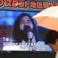 A pedestrian walks past a screen flashing news about the execution of Shoko Asahara, founder of the Aum Shinrikyo doomsday cult, in Tokyo on Friday.   AFP-JIJI