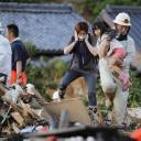 A firefighter carries a girl over debris Sunday evening in Uwajima, Ehime Prefecture.