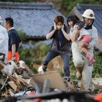 A firefighter carries a girl over debris Sunday evening in Uwajima, Ehime Prefecture. | KYODO