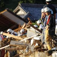Firefighters stand on debris Sunday in Uwajima, Ehime Prefecture, in an area hit by a landslide triggered by torrential rain. | KYODO