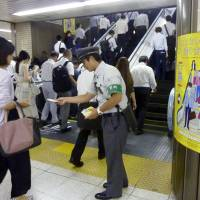 A East Japan Railway Co. employee at Tokyo Station hands out information Monday about its escalator safety campaign. | KYODO