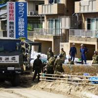 Ground Self-Defense Force personnel conduct disaster-relief operations on Sunday in Aki Ward, Hiroshima, one of the hardest-hit areas in the recent west Japan floods. | MAGDALENA OSUMI