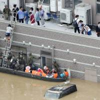 Self-Defense Forces troops rescue people stranded atop the Mabi Memorial Hospital on Sunday morning after heavy rains prompted massive flooding in Kurashiki, Okayama Prefecture. | KYODO