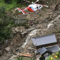 A rescue helicopter lifts up a survivor from an area hit by a mudslide in Iwakuni, Yamaguchi Prefecture, on Saturday. | KYODO