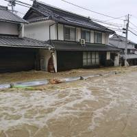 A road in the Aki district of Hiroshima city is flooded from heavy rains on Saturday morning. | KYODO