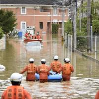 Rescuers help local residents evacuate in the flooded town of Saka, Hiroshima Prefecture, on Saturday. | KYODO