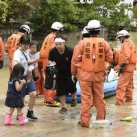 Rescuers help local residents to evacuate Saturday in the town of Saka, Hiroshima Prefecture. | KYODO