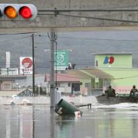 Ground Self-Defense Force personnel ride a boat to rescue locals in Kurashiki, Okayama Prefecture, on Saturday as roads remain flooded from heavy rains that hit western Japan. | KYODO