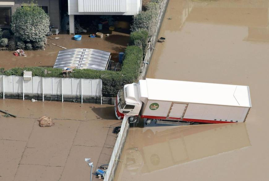 A truck that was washed away in torrential rains that spurred floods straddles a fence in Kurashiki, Okayama Prefecture, on Monday morning.