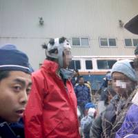 Aum Shinrikyo members wearing head gear are seen in a handout photo that appears to have been taken in March 1995, when police raided the cult's facility in then Kamikuishiki, Yamanashi Prefecture. | VIA KYODO
