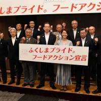 Fukushima Gov. Masao Uchibori (center), Olympic medalist Yuko Arimori (third from right) and others pose on June 20 in the city of Fukushima to announce plans to expand sales channels for Fukushima-made produce. | FUKUSHIMA MINPO