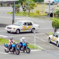 Drivers-to-be practice at Yokohama Driving School in Totsuka Ward in the city on June 22. The school is one of the remaining 1,300 authorized driving schools nationwide as the sector faces the effects of demographic change in the nation. | MAGDALENA OSUMI